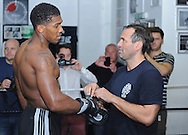 Picture by Alan Stanford/Focus Images Ltd +44 7915 056117<br /> 30/09/2013<br /> Anthony Joshua has his gloves tied by trainer Tony Sims before he performs in a media workout at Gator ABC, Hainault, Essex..