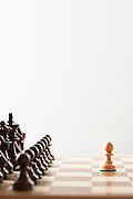 Chess game single white piece in front of black pieces