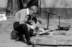 "China, Beijing, 2003. Plying his noisy trade throughout the day, a veteran pot maker hammers out aluminum kitchenware in one of Beijing's fast-disappearing ""hutongs,"" or traditional neighborhoods.."