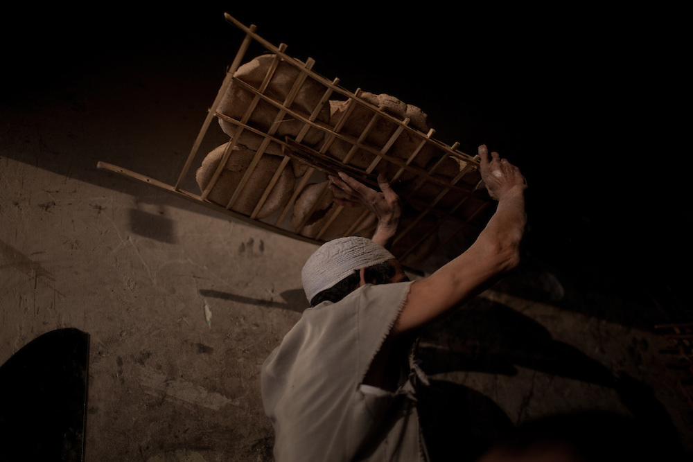 Zamir carries a rack of bread upstairs for the others to eat.