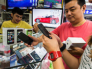 21 SEPTEMBER 2013 - BANGKOK, THAILAND:  Men look at the iPhone 5s in an electronics shop in MBK in Bangkok. Customers around the world lined up Friday to pick up Apple's new flagship iPhone 5s and its lower cost, more colorful brother, the iPhone 5c. The phones went on sale in the US and select countries beyond the US on Friday. The iPhone 5s and iPhone 5c will not be officially released in Thailand until late 2013 but the phones are available through the unofficial grey market in MBK, a huge shopping complex in Bangkok with dozens of small electronics shops. Early purchasers in Thailand pay a premium for the new iPhones, the top of the line iPhone 5s with 64 gigabytes of memory is about 38,500Baht, more than $1,200 (US).     PHOTO BY JACK KURTZ