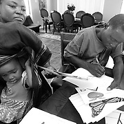 Burundian refugee Angelique Barakamfitiye holds her daughter Delphine Nibigira, 2, while her husband Jean-de Dieu Havyalimana and her learn English.