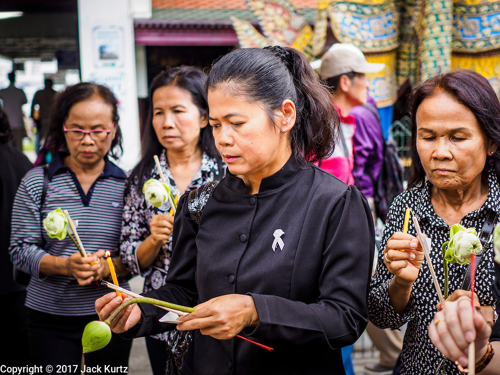 26 FEBRUARY 2017 - BANGKOK, THAILAND: A woman in black mourning clothes prays in Wat Phra Kaew, in the Grand Palace complex in Bangkok. Thousands of Thais continue to line up at the Grand Palace in Bangkok daily to pay respects to Bhumibol Adulyadej, the Late King of Thailand, who died on 13 October 2016. The government set a year long mourning period for the revered King, who will be cremated in late 2017.        PHOTO BY JACK KURTZ