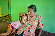 Mama Yuli embraces her granddaughter Anace (8).  They are very close. In 2004 Mama Yuli contracted the HIV virus from her husband who later died from AIDS. At her worst point, Mama Yuli was just skin and bones weighing only 22 kilograms (48 pounds). With ARV she is now healthy to work and support her family.<br /> <br /> If taken properly and regularly, ARV has been proven to prolong the survival rate of people living with HIV/AIDS and enables them to live a productive life. The Indonesian government started providing ARV therapies in 2003. In that year only 7 packages of ARV were purchased for all of Papua. Each package cost approximately $5000. Today in Indonesia this vital medication can be obtained at no cost only in Papua but only 12% of those with HIV/AIDS are undergoing ARV therapy.<br /> <br /> Despite these advances, ARV is mostly available only in cities. Collaboration between health facilities in urban centers and staffs in rural areas to make ARV more accessible for patients living in the countryside is still lacking as well as the endorsement of ARV as a legitimate medicine for HIV/AIDS. Sometimes health staff and even educational materials still provide misleading information and perception such as &quot;there is no medicine for HIV/AIDS.&quot;<br /> <br /> As a general practice health personnel often evaluate patients for their adherence in taking their medication and keeping up with appointments before allowing them to undergo ARV therapy. Indigenous Papuans tend to fall short of this assessment and fail to return for their check-up because many of them live too far from the health centers.  At times, they do not fully understand the benefits of ARV medication and the importance of taking them properly due to poor counseling from the health staff.  Also, many of them are unable to keep their appointments or take medication regularly because they still keep their status a secret from their immediate family members or spouse.