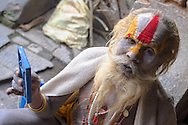 A hindu sadhu (holy man) checking his facial paint in a mirror at the temples of Pashupatinath, Nepal.
