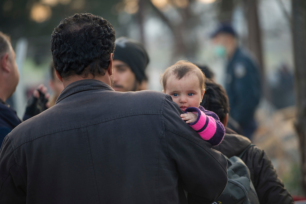 March 5, 2016 - Idomeni, Greece:  A man and his baby daughter  after hours of waiting at the  Idomeni border crossing in Greece just before crossing to Macedonia. 12,000 refugees are stuck here after Macedonia closed the border. New arrivals come in every day, making living conditions more and more difficult. (Steven Wassenaar/Polaris)