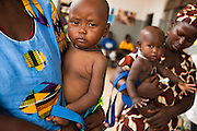 Mothers hold their children as they prepares to get him weighted at the Pujehun Government hospital in Pujehun, Sierra Leone on Friday March 19, 2010..
