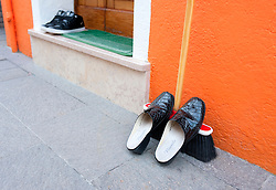 Detail of shoes resting on broom outside colourful orange house in Burano near Venice Italy
