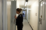 A female prison officer checks on a prisoner in her cell. HMP Send, closed female prison. Ripley, Surrey.