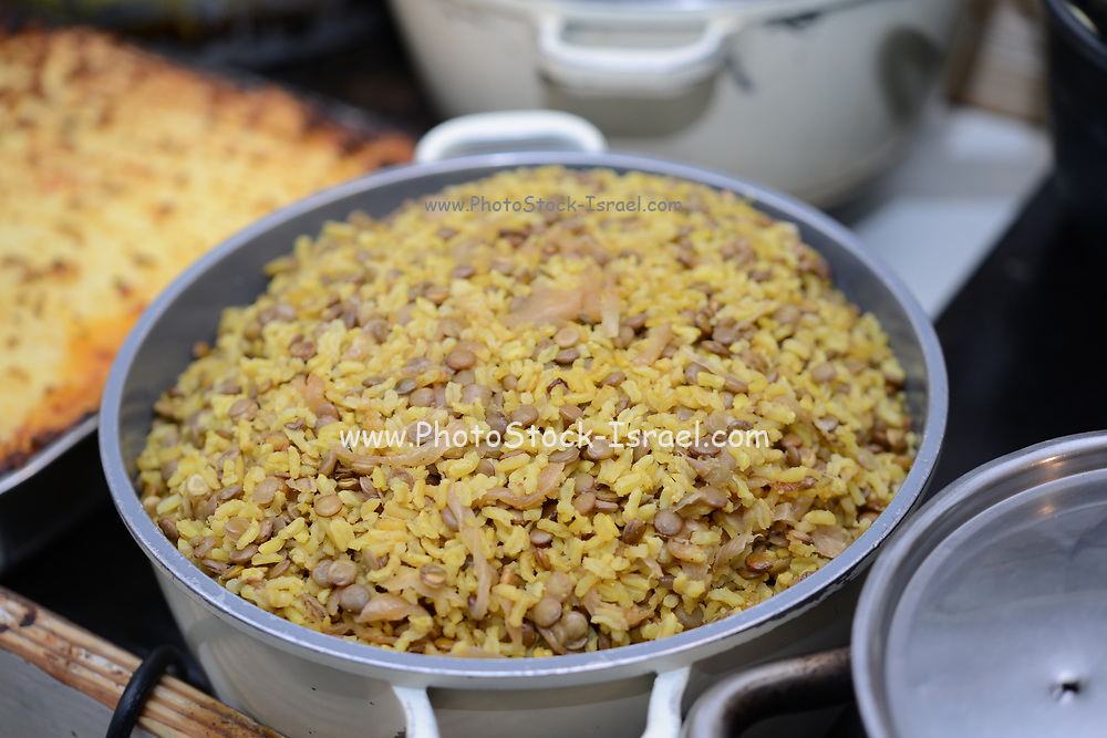 A pot of Majadara - rice with lentils and onions topped with parsley