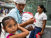"14 JULY 2013 - BANGKOK, THAILAND:  A child holds onto her mother, who sells ""Guy Fawkes"" masks to Thai White Mask protesters after a protest in Bangkok Sunday. About 150 members of the so called ""White Mask"" movement marched through the central shopping district of Bangkok Sunday to call for the resignation of Yingluck Shinawatra, the Prime Minister of Thailand. The White Mask protesters are strong supporters of the Thai monarchy. They claim that Yingluck is acting as a puppet for her brother, former Prime Minister Thaksin Shinawatra, who was deposed by a military coup in 2006 and now lives in exile in Dubai.       PHOTO BY JACK KURTZ"