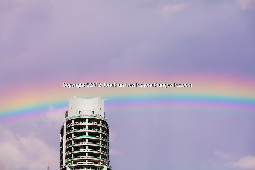 A rainbow appears in the sky behind a Miami condo building. WATERMARKS WILL NOT APPEAR ON PRINTS OR LICENSED IMAGES.