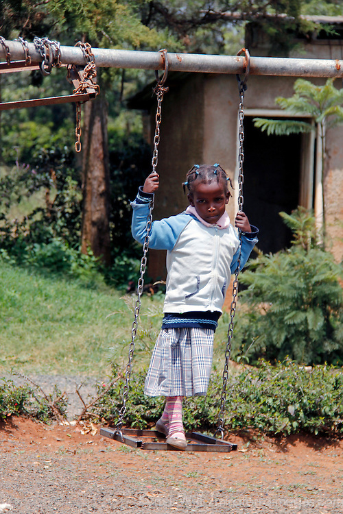 Africa, Kenya, Nanyuki. Girl on swing at the Nanyuki Children's Home.
