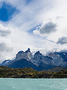 "Los Cuernos soar above turquoise Lake Pehoe in Torres del Paine National Park, Chile, South America. ""The Horns"" (about 6900 feet or 2100 meters elevation) are a pinkish-white granodiorite intrusion formed 12 million years ago topped with an older crumbly dark sedimentary rock, exposed by freeze-thaw erosion and glaciation. The foot of South America is known as Patagonia, a name derived from coastal giants, Patagão or Patagoni, who were reported by Magellan's 1520s voyage circumnavigating the world and were actually Tehuelche native people who averaged 25 cm (or 10 inches) taller than the Spaniards."