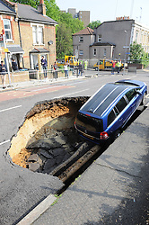 © Licensed to London News Pictures. 12/05/2016<br /> A car falls into a big sink hole on Woodland Terrace in Charlton, Greenwich, London.  The sink hole opened up at about 3am this morning. police have closed roads between Heathwood Gardens and Maryon Road.<br /> <br /> (Byline:Grant Falvey/LNP)