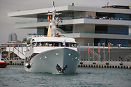Charter yacht carries VIP guests past Veles e Vents building in Port America's Cup to watch afternoon of racing; Valencia, Spain.