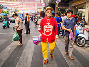 "17 FEBRUARY 2015 - BANGKOK, THAILAND:  A man dressed in his New Year's outfit walks down Yaowarat Road in Bangkok's Chinatown district. Chinese New Year is February 19 in 2015. It marks the beginning of the Year of Sheep. The Sheep is the eighth sign in Chinese astrology and the number ""8"" is considered to be a very lucky number. It symbolizes wisdom, fortune and prosperity. Ethnic Chinese make up nearly 15% of the Thai population. Chinese New Year (also called Tet or Lunar New Year) is widely celebrated in Thailand, especially in urban areas like Bangkok, Chiang Mai and Hat Yai that have large Chinese populations.      PHOTO BY JACK KURTZ"