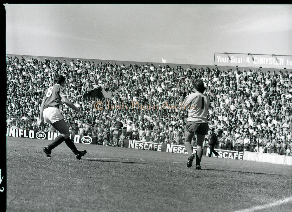 League of Ireland vs Liverpool FC.    (M87)..1979..18.08.1979..08.18.1979..18th August !979..In a pre season friendly the League of Ireland took on Liverpool FC at Dalymount Park Phibsborough,Dublin. The league team was made up of a selection of players from several League of Ireland clubs and was captained by the legendary John Giles. Liverpool won the game by 2 goals to nil..The scorers were Hansen and McDermott...Liverpool goalkeeper, Ray Clemence, clears the ball before the arrival of Cathal Muckian.