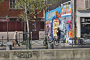 Graffiti artist at work on the Quai de Valmy along the Canal Saint-Martin in the 10th arrondissement of Paris, France. The Canal Saint-Martin is a 4.6km long waterway between the Canal de l'Ourcq and river Seine, built 1802-25 to provide a fresh water source to the city and provide a trade route for canal barges. Picture by Manuel Cohen
