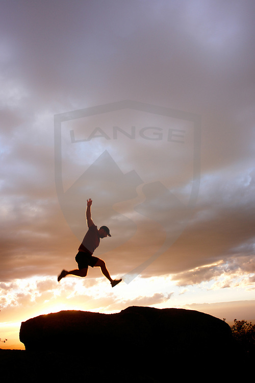 nature scenery landscapes and inspiring concepts: anonymous silhouette man jumping into sunset sky, sandia mountains, albuquerque, new mexico, usa, vertical, copy space, red, orange