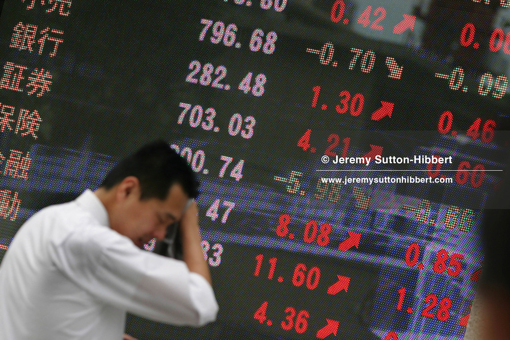 Japanese business man, known as salaryman, watches a bank stocks and shares monitor screen, showing the latest values of commodities, in Marunouchi district, Tokyo, Japan.