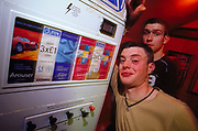 Two young men leaning against Durex condom machine at Inertia Derry Northern Ireland March 2002