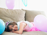 Young girl (7-9) lying on sofa with balloons smiling