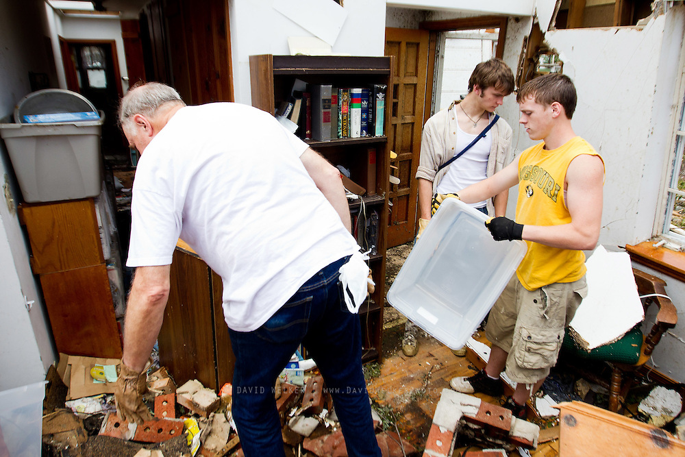 May 25, 2011- Pastor Leon Stump (left) and two youth from his church, Micah Lowery (front) and Levi Cloud (back) from Joplin, Missouri work through the debris left in Stump's home after a Tornado came through the town on Sunday, May 22, 2011. Credit: David Welker / TurfImages.com