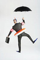 Middle-aged businessman in flippers inflatable rubber ring snorkel and goggles waddling carrying briefcase and umbrella back view