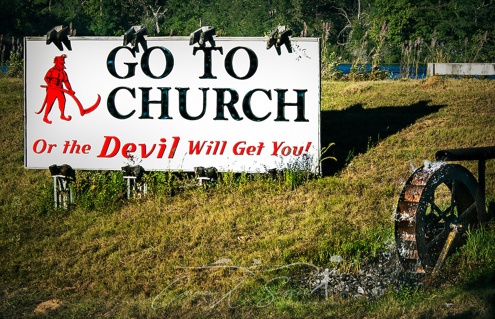 "A roadside sign warns drivers along Alabama Highway I-65 North in Deatsville that they need to to church the avoid the wrath of the Devil. The sign was erected by the late W.S. ""Billy"" Newell in the late 1980's as a way to ""wake up the people,"" Newell told NPR in 2005. Newell briefly changed the sign to, ""We Love Lucy,"" when 2006 gubernatorial candidate Lucy Baxley. Newell died in 2009. (Photo by Carmen K. Sisson/Cloudybright)"