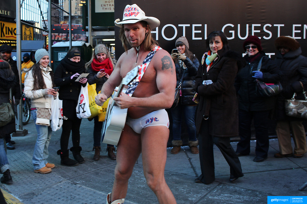 The Naked Cowboy makes the most of the influx of people during Super Bowl week activities in Times Square, New York, USA. 29th January 2014. Photo Tim Clayton