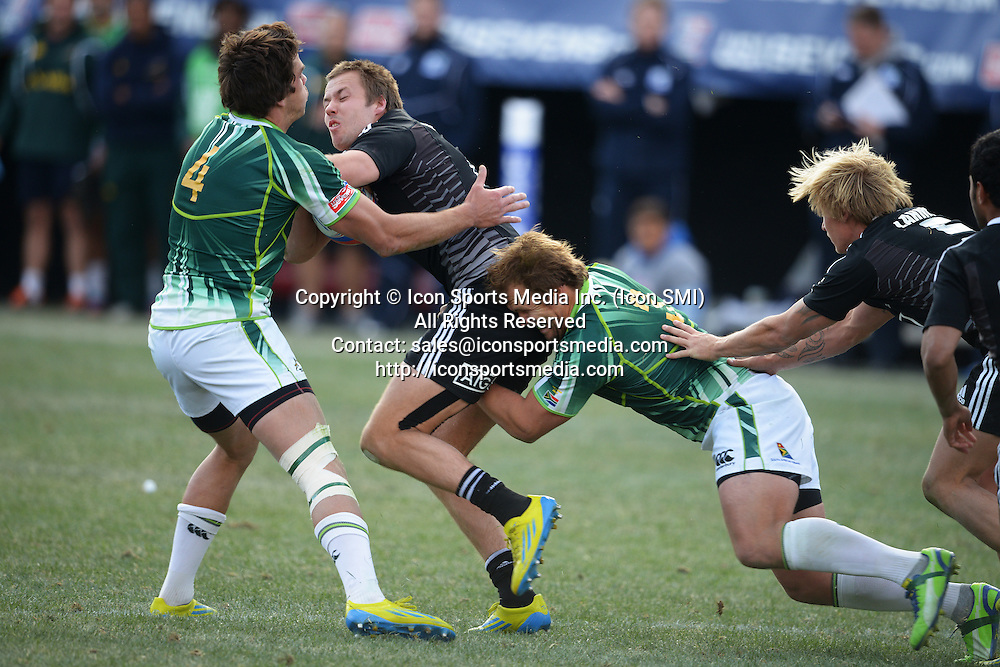 10 February 2013: Tim Mikkelson (2) of New Zealand gets tackled by Warren Whiteley (4) and Frankie Horne (3) of South Africa in the finals of round 5 of the HSBC Sevens World Series of Rugby at Sam Boyd Stadium in Las Vegas, Nevada. South Africa defeated New Zealand 40-21.