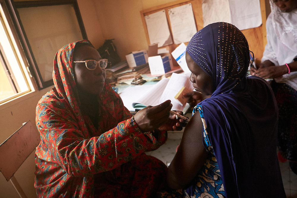 Medical assistant Yayé Aissa Boubacar injects a tetanus vaccination for pregnant expecting mother Mariama Yacouba, 20 years old at the Saguia health centre, Niamey, Niger on February 16, 2016. The Saguia Health Centre serves a population of 9353 people thanks to a team of 20 people including 3 nurses and 4 midwives who receive pregnant women for prenatal consultations from Monday to Friday. During the first prenatal consultation the pregnant women receive a first dose of vaccinations and a booster on their second consultation. The third, fourth and fifth doses are administered later. This vaccination reinforces the immunity of the mothers and their children. The vaccination for against tetanus is free for pregnant women children under 5 years of age. To reach the population whom do not frequent health centres the district health department organise consultations in villages once per month that are more than 15km from the health centre.