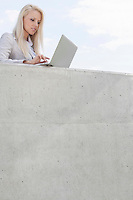 Beautiful young businesswoman using laptop on terrace against sky