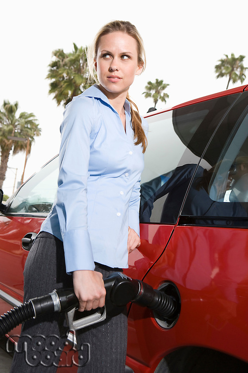 Woman by car with fuel pump