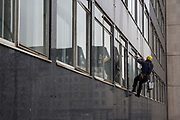 An abseiling window cleaner cleaning the windows of the office block at number 11 York Rd, next to Waterloo train station in Lambeth, London.  (photo by Andrew Aitchison / In pictures via Getty Images)