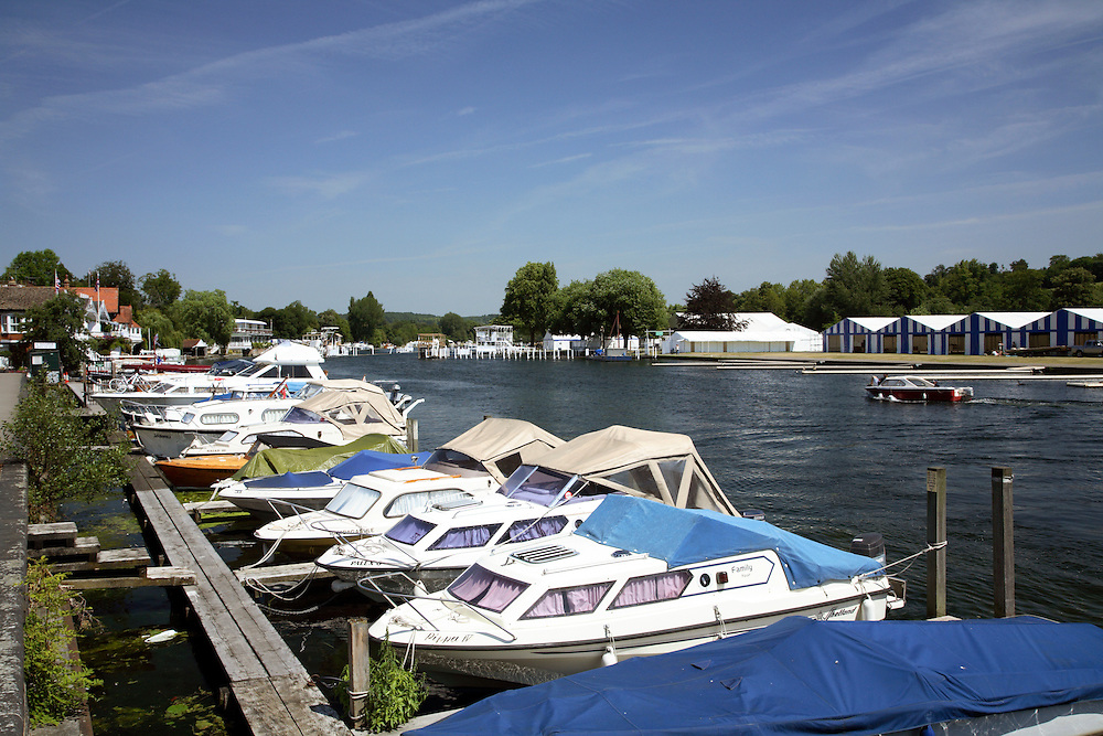 Photograph taken from the bank of the river Thames in the centre of Henley on Thames showing the view downstream of the Royal Regatta course with moored boats in the foreground.  The image was taken during a hot and sunny summer day.
