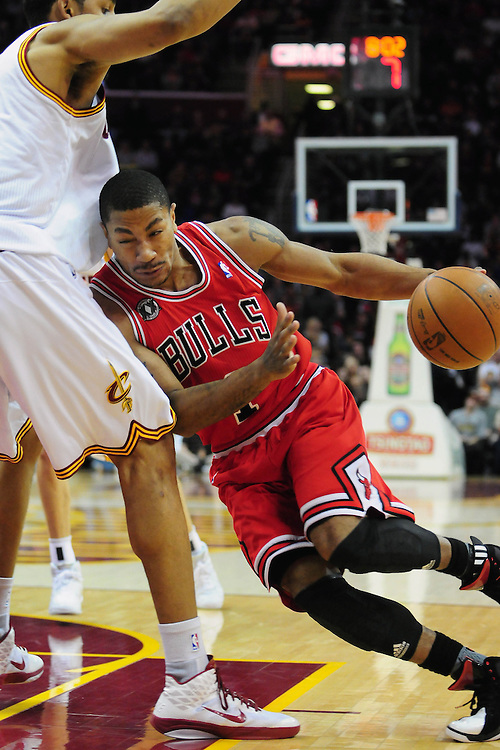 April 8, 2011; Cleveland, OH, USA; Chicago Bulls point guard Derrick Rose (1) drives into Cleveland Cavaliers center Ryan Hollins (5) during the first quarter at Quicken Loans Arena. Mandatory Credit: Jason Miller-US PRESSWIRE