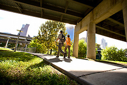 Couple walking along a path underneath a freway overpass in Buffalo Bayou park in Houston, Texas