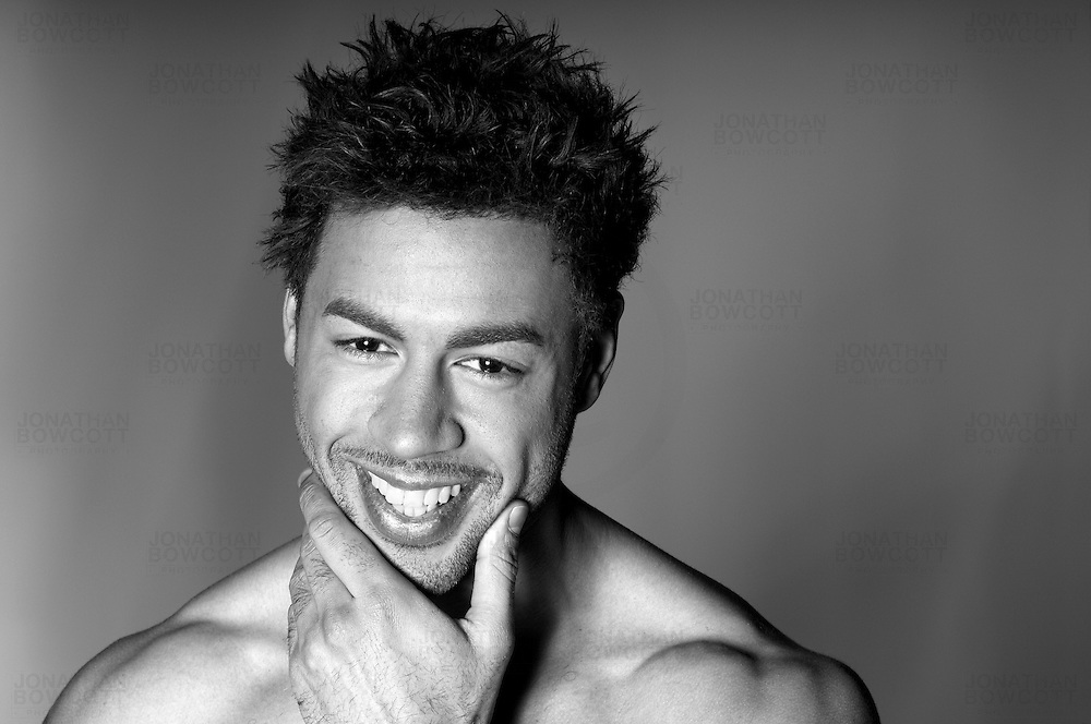 Classic black and white headshot of male model smiling with hand on chin