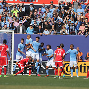 Chris Tierney, New England, see his free kick hit the head of Steven Mendoza, NYCFC and wrong foot the keeper for the equalizing goal in the 1-1 draw during the New York City FC Vs New England Revolution, MSL regular season football match at Yankee Stadium, The Bronx, New York,  USA. 26th March 2016. Photo Tim Clayton