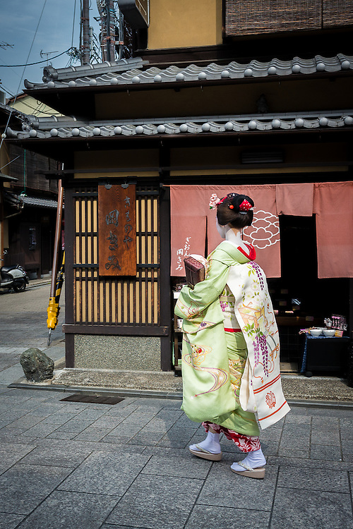 A maiko walks through Hanami Koji, the most famous street in the district of Gion.
