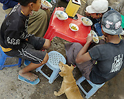 Young boys enjoy lunch in Mandalay, Myanmar as a small dog awaits a handout.