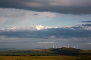Wind turbines catch the light under a stormy landscape from Craig Airie Fell, Borders, Scotland