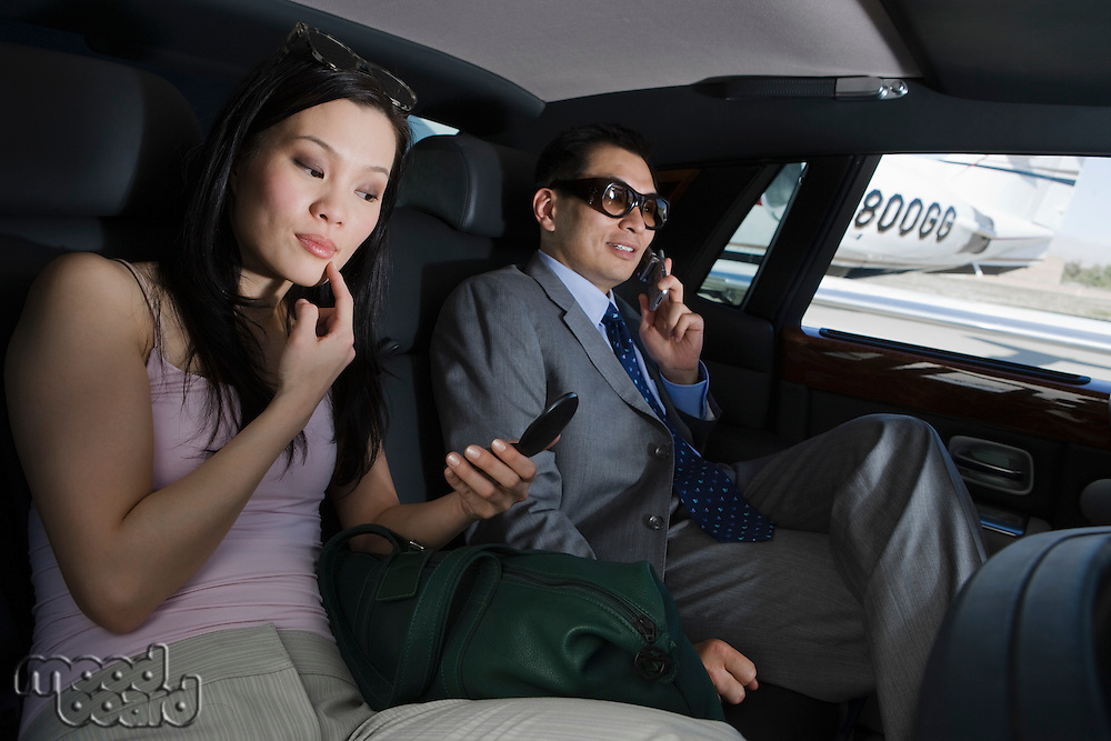 Mid-adult Asian businessman and businesswoman inside limousine.