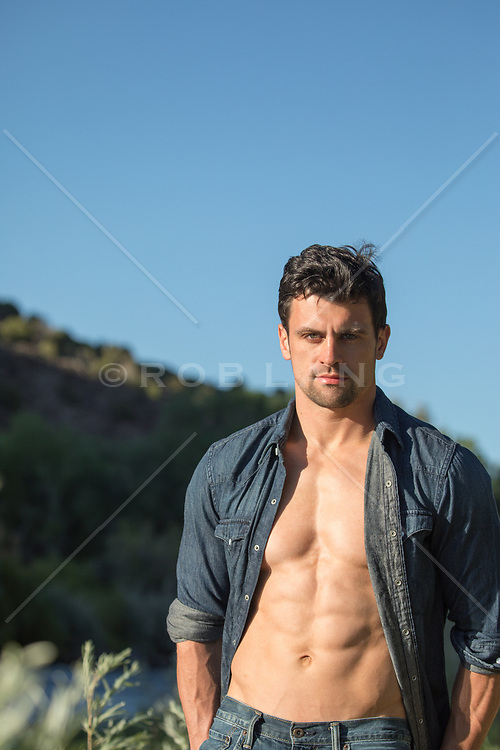 sexy man with green eyes and dark hair outdoors