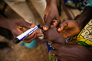 A community health nurse marks a child's finger with indelible ink after vaccinating him against polio in the village of Gbulahabila, northern Ghana on Wednesday March 25, 2009.