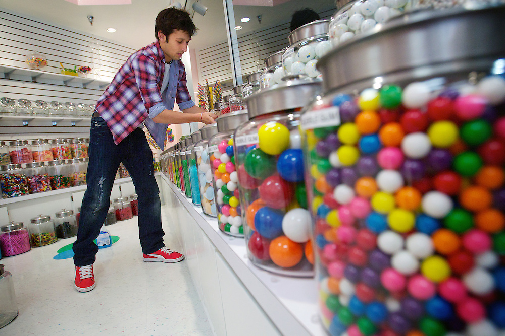 Devin Sommer helps organize candy jars Thursday at Mrs. Honeypeep's Sweet Shop in the Coeur d'Alene Resort Plaza Shops.