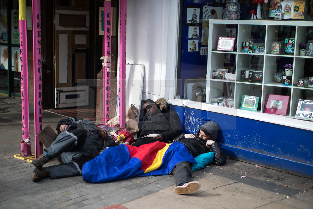 © Licensed to London News Pictures . 03/04/2017 . Manchester , UK . Three people lie slumped in the middle of the day outside a shop on Piccadilly , in Manchester City Centre . The city has experienced a growth in the number of people sleeping rough and emergency services report spikes in the need to tend to people high on Spice . Photo credit : Joel Goodman/LNP
