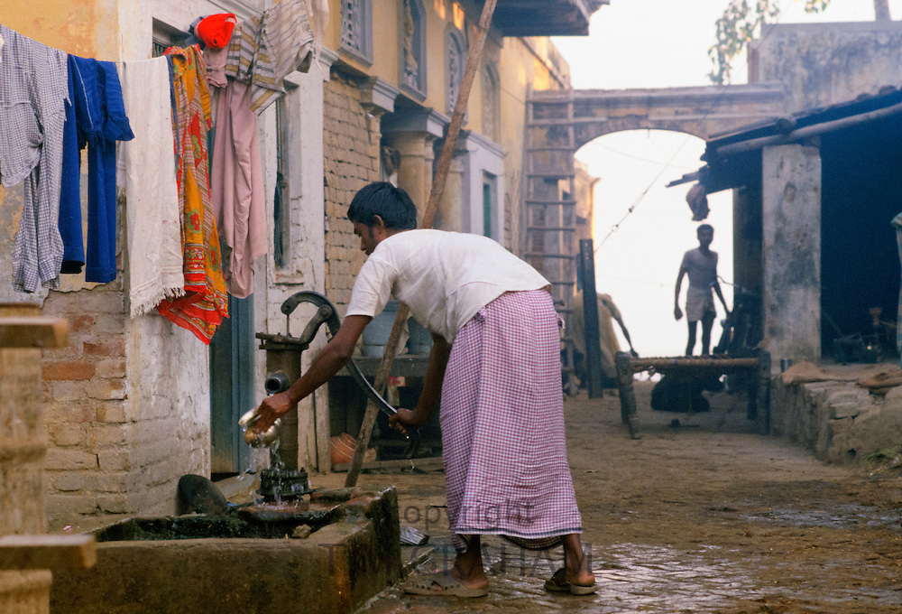 Life on the streets for Indian family pumping water in street in India